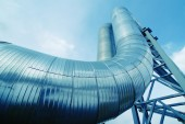 Zona industrial, tuberías de acero y válvulas contra el cielo azul — Foto de Stock