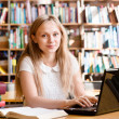 Portrait of a pretty female student with laptop in library — Stock Photo #73975941