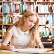 Young female student doing assignments in library — Stock Photo #73975969