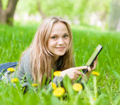 Girl lying on grass with tablet computer and looking at camera — Stock Photo