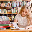 Girl doing assignments in library — Stock Photo #75285285