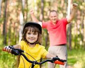 Father teaching his daughter to ride a bike — Stock Photo