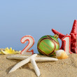New year 2015 sign with seashells, starfish and christmas ball on a beach sand — Stok fotoğraf #60597733
