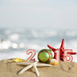 New year 2015 sign with seashells, starfish and christmas ball on a beach sand — Foto de Stock   #60597749