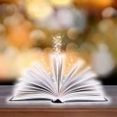 木の板と暗い背景に光のボケ味を持つ開かれた本 — ストック写真