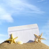 Seashells and starfish with open envelope with blank letter on sand beach — Stock Photo