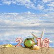 New year 2016 sign on a beach sand with seashells, starfish and christmas ball — Stok fotoğraf #70637841