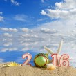 New year 2016 sign on a beach sand with sea shells, starfish and christmas ball — Stok fotoğraf #70637899