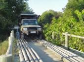 Off-road vehicle on wooden bridge — Stock Photo