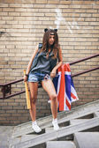 Bad girl holding a baseball bat and British flag at street. — Stockfoto