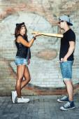 Bad sexy young  woman with leather cat ears threatening baseball  bat guy. — Stock Photo
