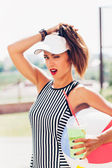 Sporty woman drinking water against the sports ground — Stock Photo