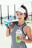 Sporty woman with skateboard drinking water against the sportsground — Stockfoto