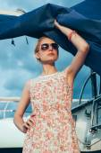 Blonde girl in flower dress and sunglasses holding  boat sails — Stockfoto
