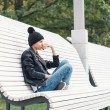 Beautiful young female sitting on a park bench — Stock Photo #57536249