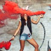 Naughty girl in pink rabbit ears with red smoke bombs — Zdjęcie stockowe