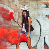 Naughty girl in pink rabbit ears with red smoke bombs — Stock Photo