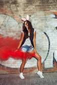 Sexy girl in pink rabbit ears dancing  with red smoke bombs — Stock Photo