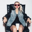 Sexy  blonde woman in sunglasses sit on black office chair and drink hot coffee — Stock Photo #61289977