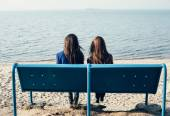 Two slender girl relaxing on shore of sea on evening — Stockfoto