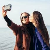 Two girlfriends doing selfie on the beach in front of the sea — Stock Photo