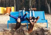 Two funky friends making pictures lying upside down on bench  — Stock Photo