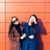 Two beautiful young girl friends in  coats posing near red wall — Stock Photo