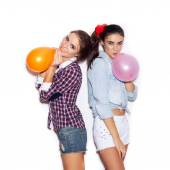 Two girlfriends inflate colored balloons — Stock Photo