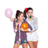 Two happy girls have fun with colorful colored balloons — Stock Photo