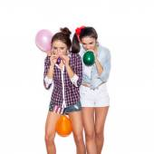Two pretty young women inflate colored balloons — Stock Photo
