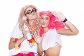 Funny girls in colored wigs and glasses play the ape — Stock Photo