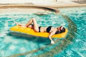 Woman with perfect tanned body lying on yellow air mattress — Stock Photo