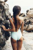 Girl standing on coastal sea rocks — Stock Photo