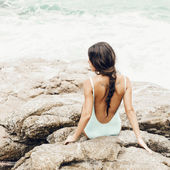 Young woman in a swimsuit sitting on the shore — Stock Photo