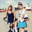 Fashion portrait of attractive young girls with bicycle — Stock Photo #79434894
