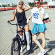 Fashion portrait of attractive young girls with bicycle — Stock Photo #79435002
