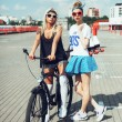 Fashion portrait of attractive young girls with bicycle — Stock Photo #79435158