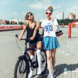 Fashion portrait of attractive young girls with bicycle — Stock Photo #79435182