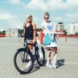 Fashion portrait of attractive young girls with bicycle — Stock Photo #79435384