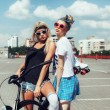 Fashion portrait of attractive young girls with bicycle — Stock Photo #79435596
