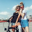 Fashion portrait of attractive young girls with bicycle — Stock Photo #79435662