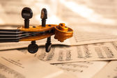Old violin lying on the sheet of music — Stock Photo