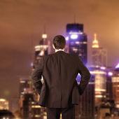 Biznesmen w kolorze patrząc do miasta w nocy — Zdjęcie stockowe