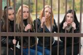 Women looking from behind bars — Stockfoto