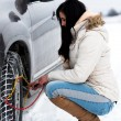 Woman putting winter tire chains on car wheel — Foto Stock #61822835