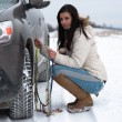 Woman putting winter tire chains on car wheel — Foto Stock #61893045
