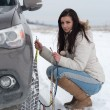 Woman putting winter tire chains on car wheel — 图库照片 #61893049