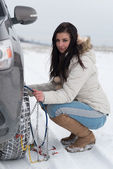 Woman putting winter tire chains on car wheel — Stock Photo