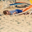 Toddler dressed as a sailor lying from a top of a sunbed on a be — Stock Photo #65973521