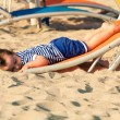 Sweet toddler dressed as a sailor lying from a top of a sunbed o — Stock Photo #65977483